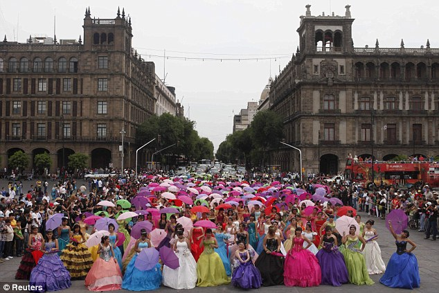 Happy: Girls dressed in evening gowns pose for photographs at Zocalo square in Mexico City for the rite-of-passage party