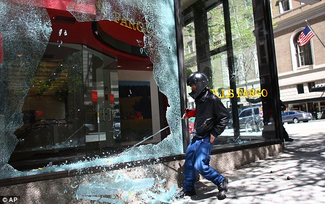 Shattered: A disguised activist pulls away more sheet glass from the window of a Wells Fargo branch in downtown Seattle today