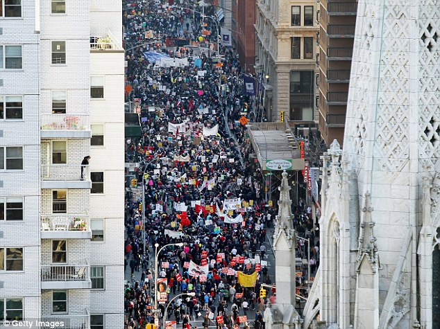 City at a standstill: Protesters march down Broadway towards Wall Street today as the Occupy movement shows no sign of dissipating