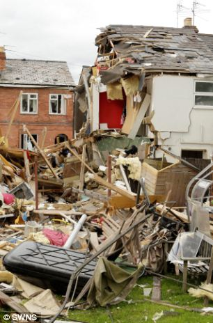 Strewn: The house's contents left piled across the street and in the garden after being blown 50ft into the air