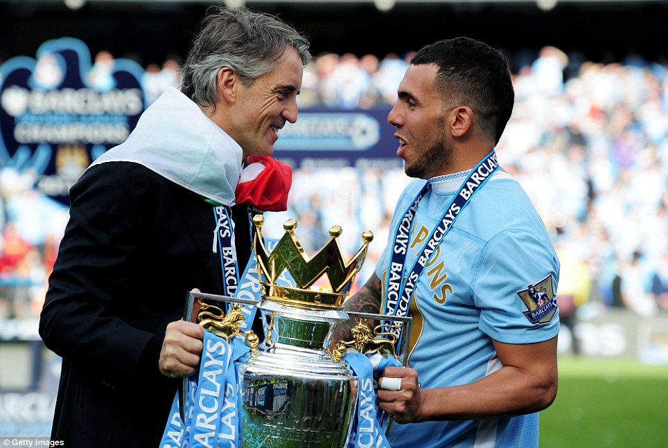 Beautiful moment: Mancini and Carlos Tevez hold the trophy after putting their troubles behind them