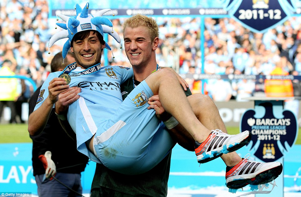 Show us your medal: Joe Hart holds team-mate David Silva as they enjoy their moment