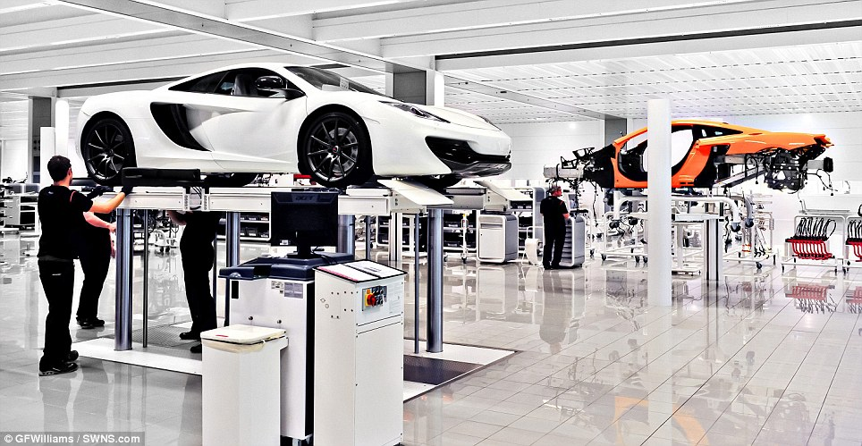 On a high: The cars sit on individual lifts to allow the workers the move their way around the bodies of the vehicles