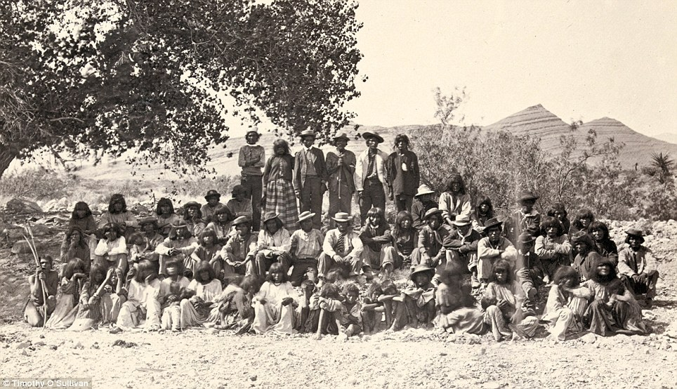 Portrait: Native American (Paiute) men, women and children pose for a picture near a tree. The picture is thought to have been taken in Cottonwood Springs (Washoe County), Nevada, in 1875