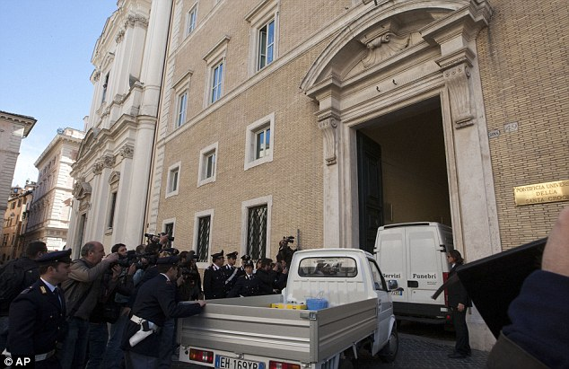 A burial service truck enters the courtyard of Sant' Apollinare Basilica, in Rome, before the tomb of mobster Enrico De Pedis was opened