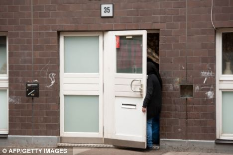 A woman stands in the door of a house in Berlin, where the dismembered body of a 30-year old woman was found
