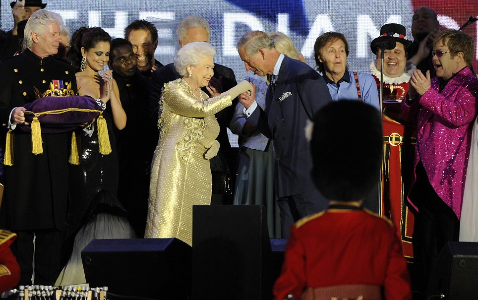Touching: Prince Charles takes the Queen's hand following the concert