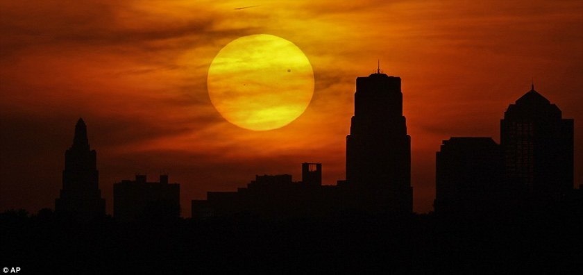 Enthralling: Venus is silhouetted as it crosses in front of the sun as it sets behind the Kansas City, Missouri skyline on Tuesday, June 5, 2012