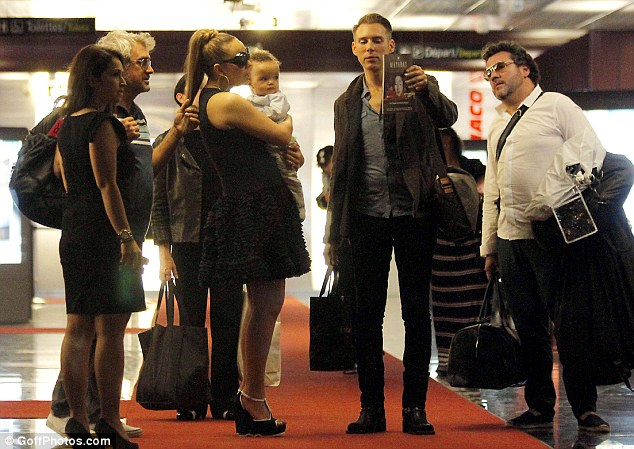 Where to? Mariah holds her son Moroccan close as she stops and chats to her entourage inside the arrivals area of the airport