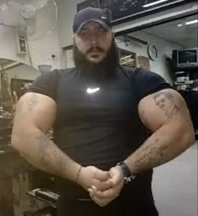 Pumped up: Areen Al Assad, with a tattoo of Bashar Assad on his bicep, is said to be one of the 'Ghost' killers roaming Syria