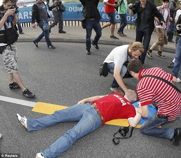 A Polish soccer fan lies on the ground after clashing with Russian supporters