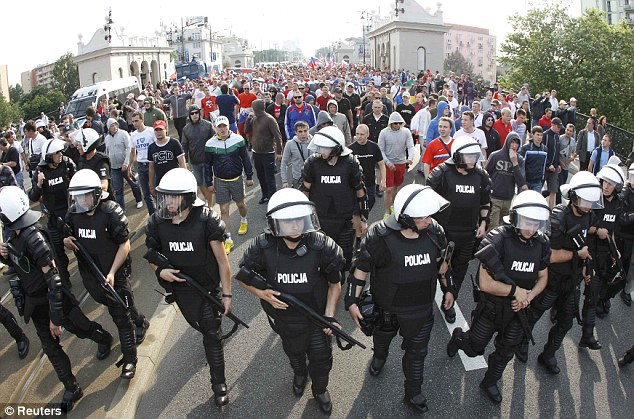 Russian football fans walk protected by Polish riot police in Warsaw