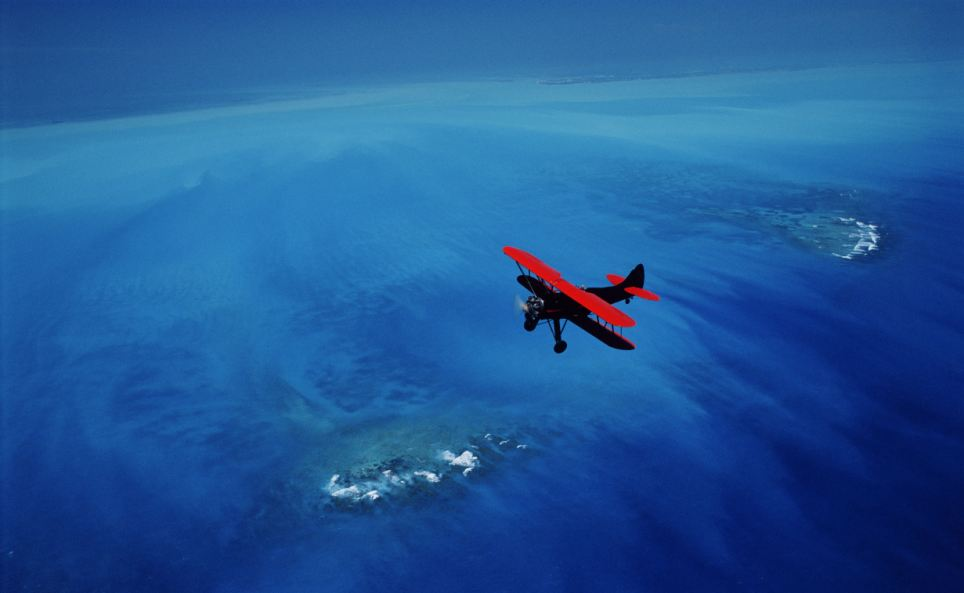 Vast and blue: A red Waco biplane over Key West and the Florida Keys National Marine Sanctuary - the birth place of the Gulf Stream