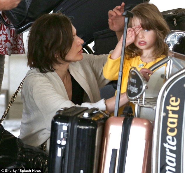 Tired eyes: The actress and model reassures her tired daughter as they prepare to return home