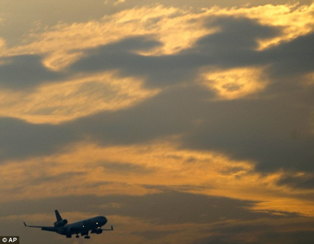 Warming up: A plane prepares to land in Newark, New Jersey on Wednesday, as the sun begin to break through the clouds on the longest day of the year