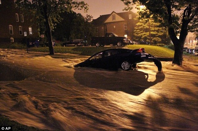 Extreme: While the East basks in sunshine, residents in Duluth, Minnesota endured torrential rain. Here, a car is stranded in floodwaters, which created mudslides and sinkholes