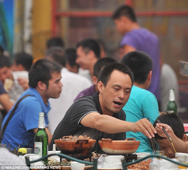 Chinese meal: Diners tuck into dishes in a restaurant which include dog