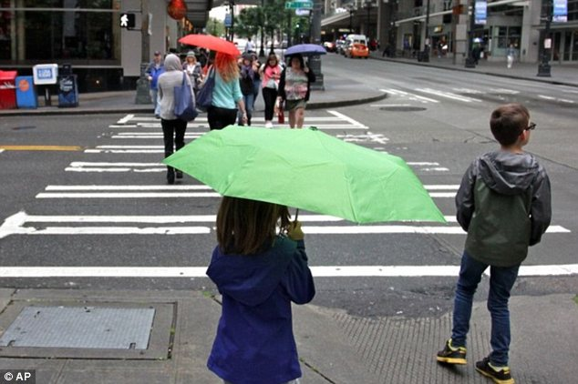 What heat?: It looks like March, not June, in Seattle as people are clad in coats and scarves, using umbrellas to shield themselves not from the bright sun but raindrops (pictured)
