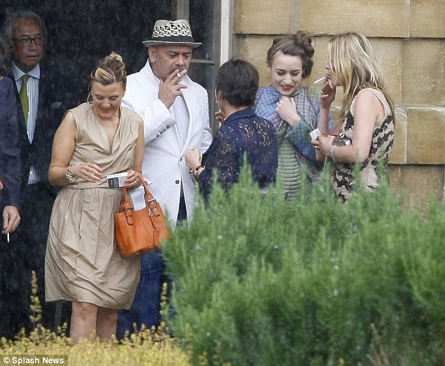 Gasping: Kate Moss (far right) and Elizabeth Jagger couldn't' wait to light up as they and Christian Louboutin stood outside Jade Jagger's wedding today