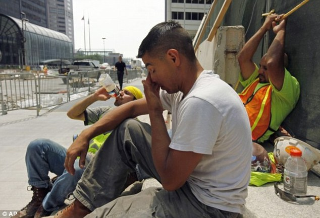 Hard work: Construction workers Santiago Gomez, Jorge Moreno, Abel Lozano take a break from the extreme heat in Chicago