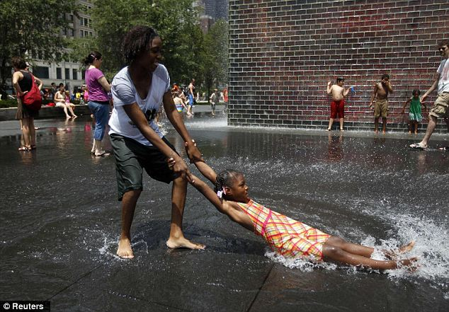 A helping hand: Kenyardia Chambers brought Kale Currin through the cool fountain in Chicago's Millennium Park on Thursday as temperatures were expected to reach 105 in the city