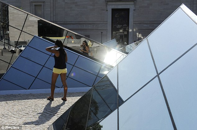 Boiling sun: A woman walks in Washington D.C., where temperatures hovered around 100 degrees
