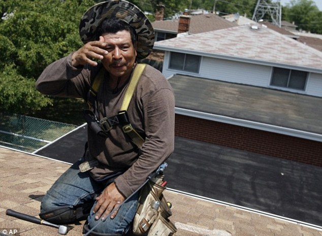 Hot work: Armando Garcia wipes his forehead while working on a roof under the sun in Des Plaines, Illinois