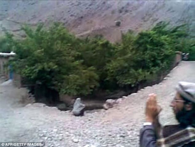 A woman, named as 22-year-old Najiba is shown sitting at the edge of a ditch wearing a grey veil, in the right hand corner a man seem to be filming something out of frame