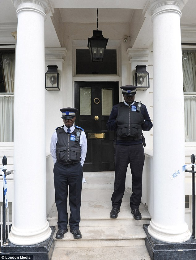 Guard: Two police community support officers stand outside the front door to the couple's Belgravia home