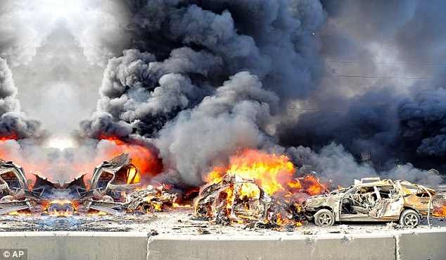 Violence: Flames and smoke raise from burning cars after two bombs exploded, at Qazaz neighborhood in Damascus, Syria, as the country descends into civil war