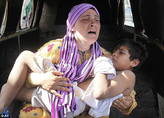 Bloodshed: A Syrian woman, cries as she carries her injured son who was shot in his hand by the Syrian border guard when they were crossing a river from Syria to Lebanon