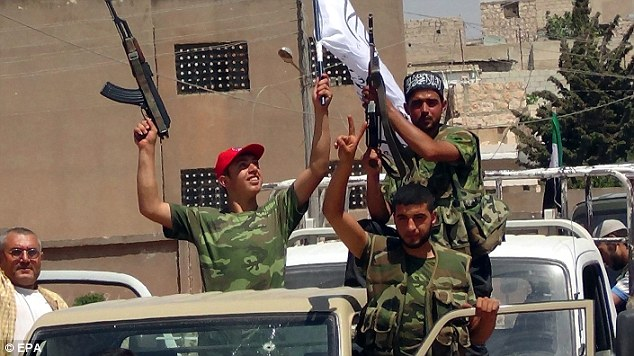 Brutal: With Syria's civil war into the country's two main urban centers, an activist group said the death toll had risen to more than 19,000. Syrian rebels are pictured celebrating near Aleppo