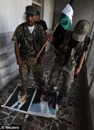 Disrespect: Free Syrian Army soldiers step on portraits of President Bashar al-Assad at the Bab Al-Salam border crossing to Turkey