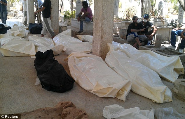 Casualties: Bodies are laid out at a cemetery in the Qabon district of Damascus. Opposition activists say at least 20 unarmed men were executed by Syrian troops