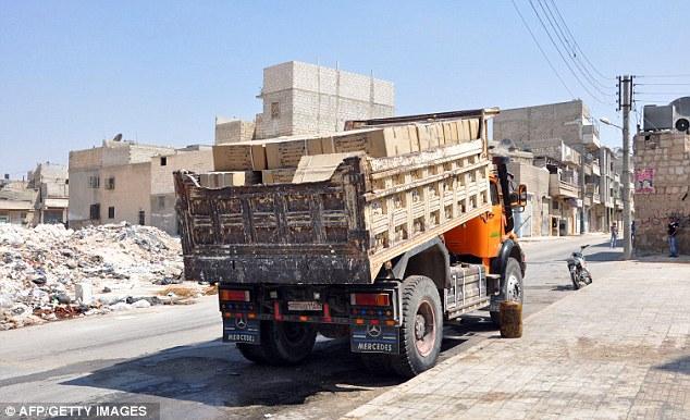 Preparado: Un camión cargado con cajas etiquetadas máscaras de gas en árabe se sienta estacionado fuera de una base de las fuerzas rebeldes en Aleppo