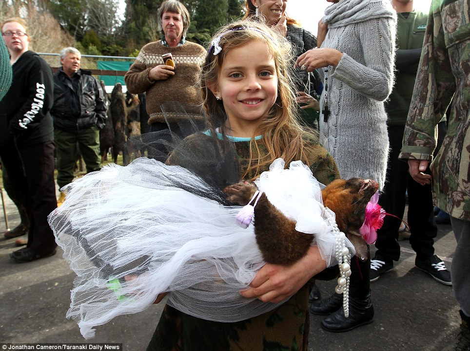 Wedding belle: This little girl looks proud as she clutches a dead possum wearing a bridal gown