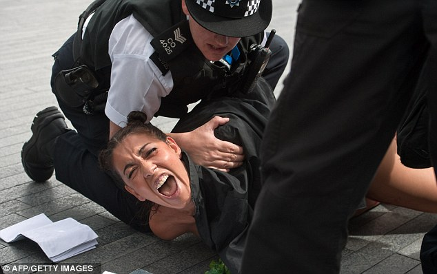 Cry: A woman screams as police officers hold her on the ground after a protest outside City Hall