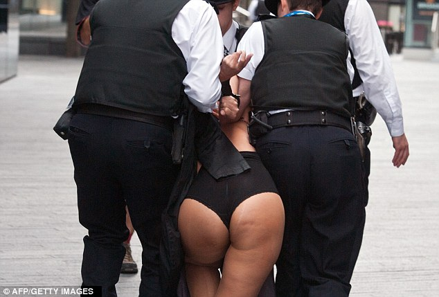 Detained: A protester in her underwear is led from the scene in handcuffs