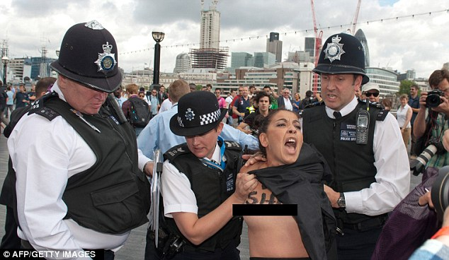 TOPLESS BABE LEAD AWAY BY THE SPOILSPORT POLICE Activists: The FEMEN demonstrators organised an 'islamic marathon' to demonstrate against 'islamic regimes' they say are being supported by the IOC.