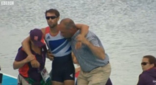 Shattered: Sir Steve Redgrave and a volunteer hold up exhausted Mark Hunter as he attempts to get him moving again after his efforts during the mens double sculls final