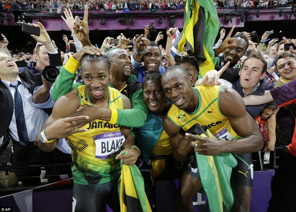Star attractions: Jamaican sprinters Usain Bolt (right) and Yohan Blake (left) are mobbed by fans after winning gold and silver in the race