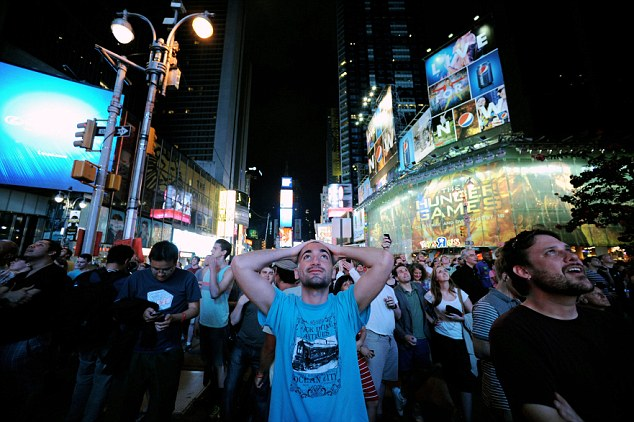 Spectators in New York's Time Square react as they watch the announcement of the Mars science rover Curiosity, successfully landing