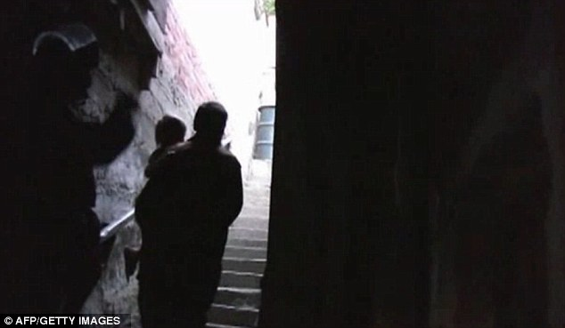 Seeing the light: The video shows children being led up the stairs of the underground tunnel - possibly for the first time in their lives