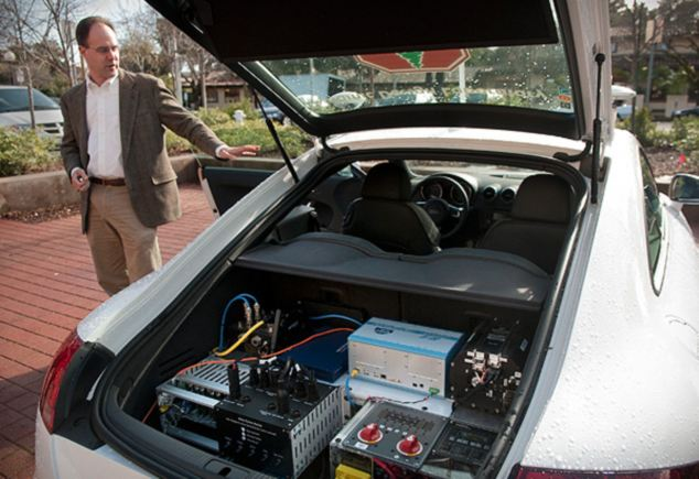 Graduate research team leader Chris Gerdes shows off the systems carried onboard the autonomous car, a modified Audi TTS