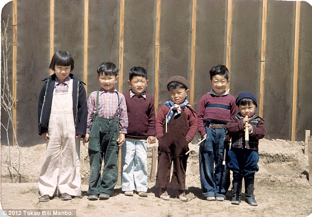 A group of children line up for a photo in front of a barrack wall. Billy Manbo is on the far right. Photo by Bill Manbo