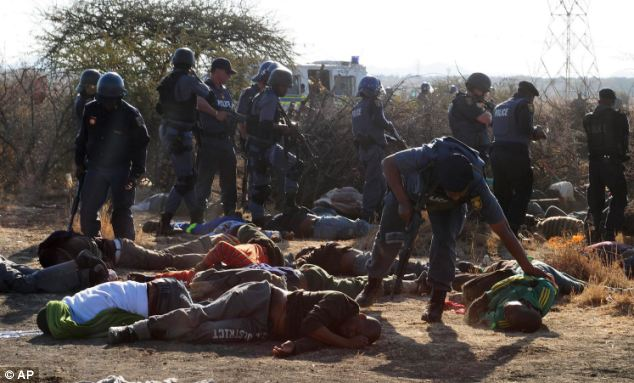 Aftermath: South African protesters lie motionless on the ground as heavily armed police officers check them at the Lonmin Platinum Mine near Rustenburg, South Africa