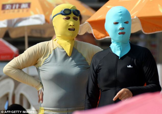 Stay away from the sun: Chinese beachgoers wearing body suits and protective head masks, dubbed 'face-kinis' by Chinese netizens, on a crowded public beach in Qingdao, northeast China's Shandong province