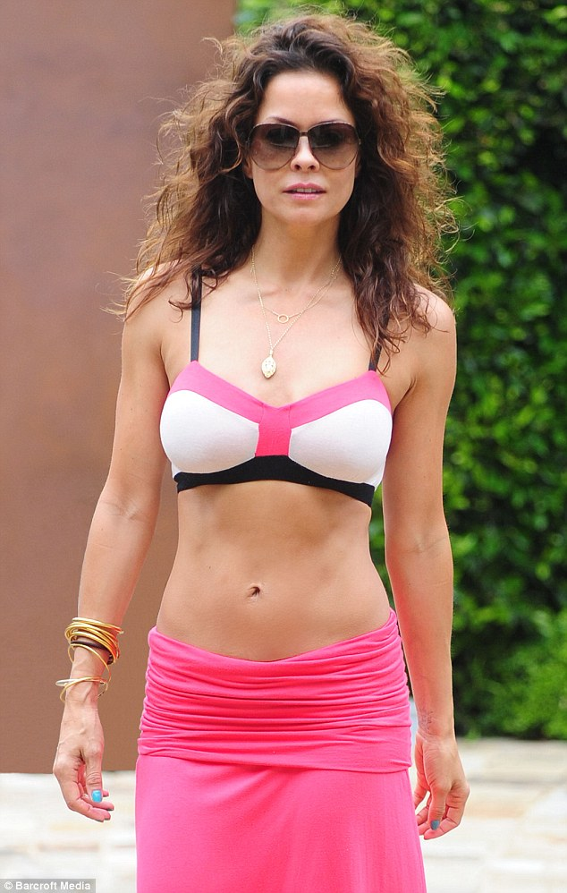 Pretty in pink: Posing at her Beverly Hills home, the brunette star displayed her toned abdominal muscles in the pink two-toned ensemble featuring black trim