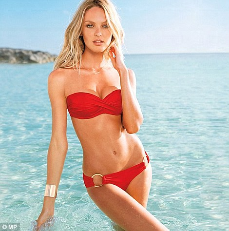 Lady in red: Candice looked flawless in a barely-there red bikini with gold bangle as she posed in the sea