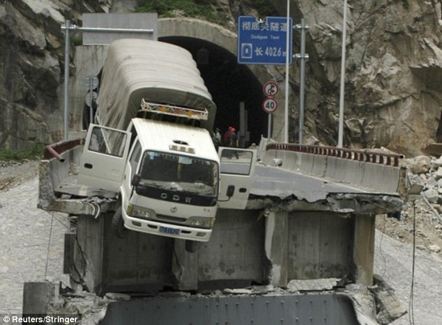 Shocking: A truck hangs precariously on the edge of a bridge in China after structure's collapse in Sichuan province in 2009
